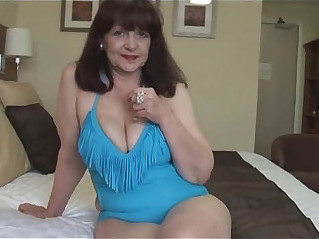 Attractive big tits mature lady in tight swimsuit playing on fitness ball